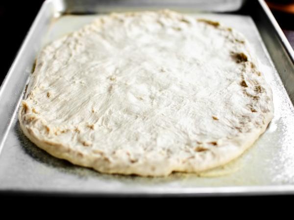 Кладём в круглую форму или на противень, смазанный маслом и присыпанный манкой либо кукурузным крахмалом – это придаст основе ещё более хрустящую корочку и пицца получится вкуснее.
