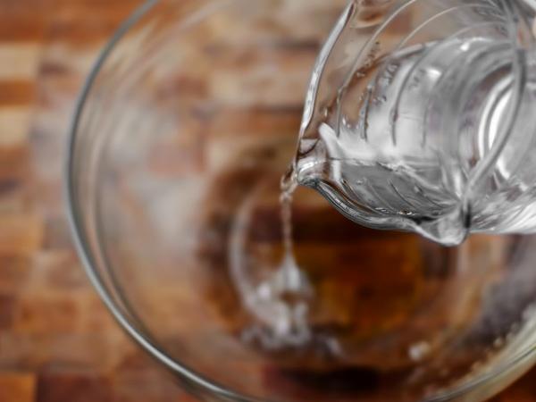 Заливаем мёд стаканом тёплой воды и быстро взбиваем венчиком до однородности.