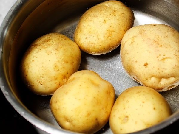 Картофель промываем под проточной водой, при необходимости используем мягкую щётку, чтобы удалить всю грязь с поверхности и не соскоблить кожуру. Складываем картошку в достаточную по вместимости кастрюлю и заливаем холодной водой так, чтобы покрыть картофель на 2-3 см.