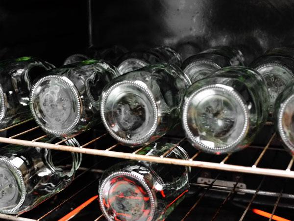 Огурцы, купленные на рынке либо в магазине, замачиваем на пару часов в холодной воде перед засолкой. Огурцов нужно столько, чтобы в 4 литровые банки вошли приправы и огурцы. Готовим рассол – 1,5 литра воды, 170 грамм сахара, 170 мл 9% уксуса, 2 столовые ложки соли. Рассол доводим до кипения. Снимаем с огня, вливаем 260 грамм томатного соуса или кетчупа, размешиваем, и рассол готов. Займёмся стерилизацией банок. Для этого разогреваем духовку до 100 градусов. Промываем банки и крышки. Помещаем пустые банки в разогретую духовку для стерилизации минимум на 15 минут.